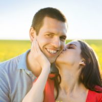 happy-young-couple-in-love-kissing-in-yellow-colza-field